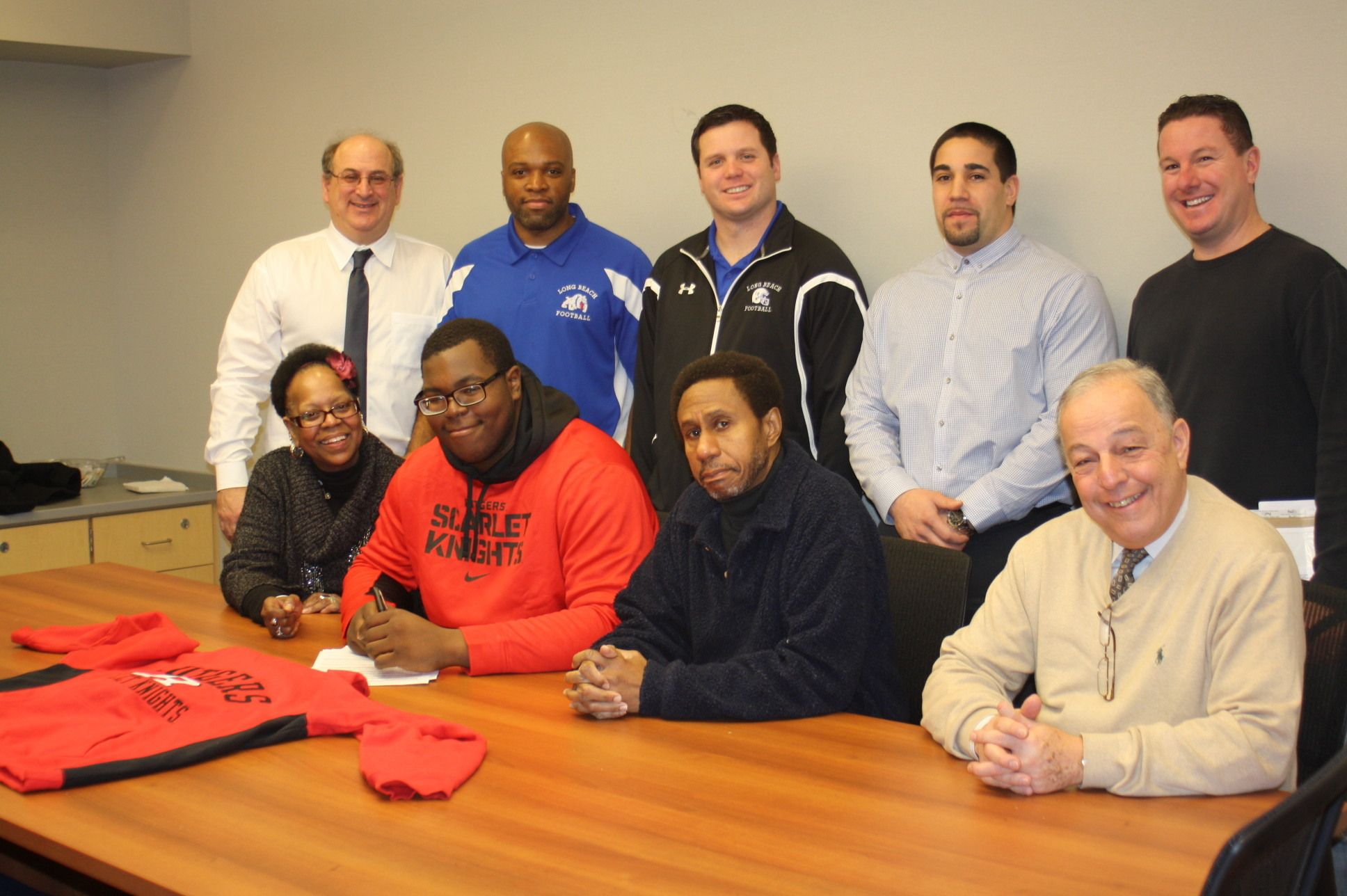 Long Beach High School senior Tariq Cole, seated second from left, signed a letter of intent to play college football at Rutgers University. He was joined by his parents, Queen, far left, and Hunter, second from right, along with District Director of Athletics Arnold Epstein, clockwise from top left, assistant coach Ian Butler, head coach Scott Martin, volunteer coach Rocco Tenebruso, guidance counselor Michael Vitale, and Interim Principal Neil Lederer.