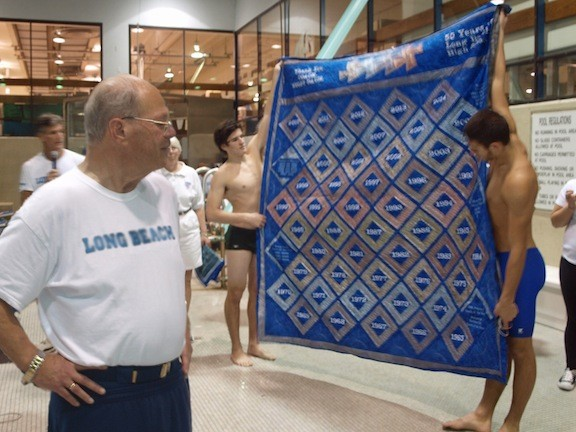 Long Beach boys varsity swim team members presented coach Woody Davis with a blanket commemorating his 50-year coaching career.