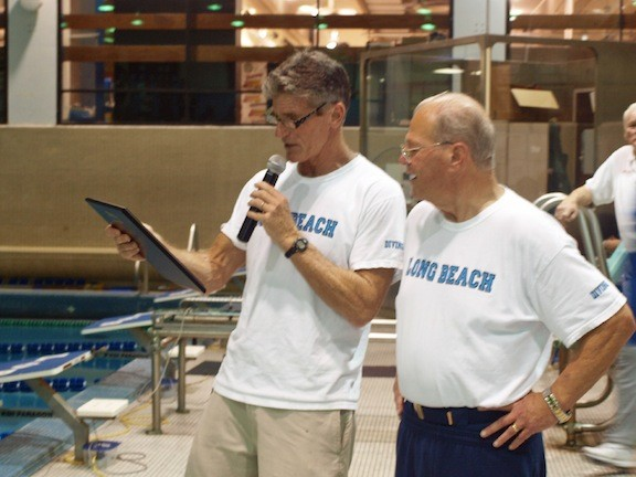 John Skudin, left, head coach of the Long Beach boys varsity swim team, presented coach Woody Davis with a plaque commemorating his 50-year career as a boys swim coach.