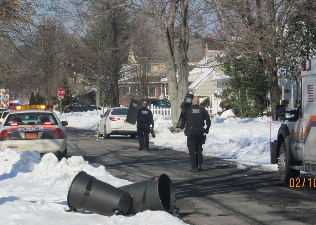 Police officers carried riot shields Monday afternoon on Stevens Avenue in North Merrick.