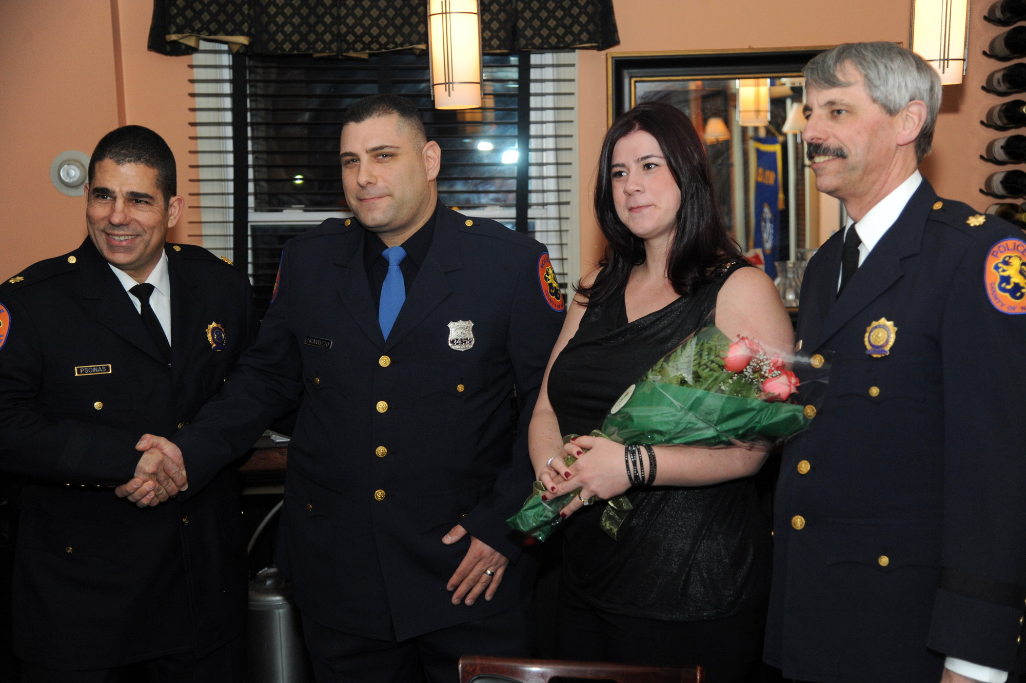 During Kiwanis Club of the Five Towns Police Awards Night, Deputy Inspector Robert Psoinas, left, congratulated police officer Santo Scavuzzo and his wife, Lisa. At right was Deputy Inspector Kenneth Hettler.