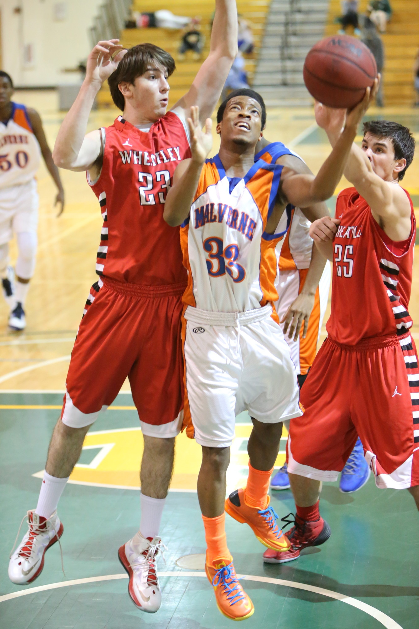 Malverne's Tyree Kingston, left, releases a shot between two Wheatley defenders.