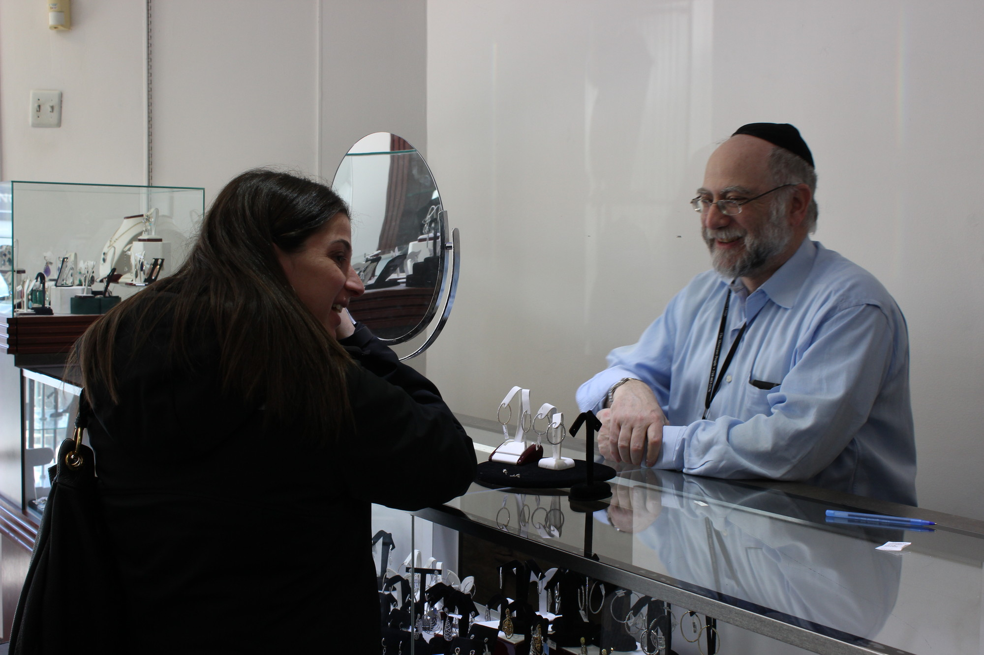 Howard Chait, owner of Goldmine Jewelry in Cedarhurst, assisted Danit Taub of Woodmere as she tried on a pair of hoop earrings.