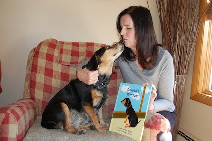 Susan Infield with her dog, Dakota, the inspiration behind her first published book, a children's story about the benefits of pet adoption.