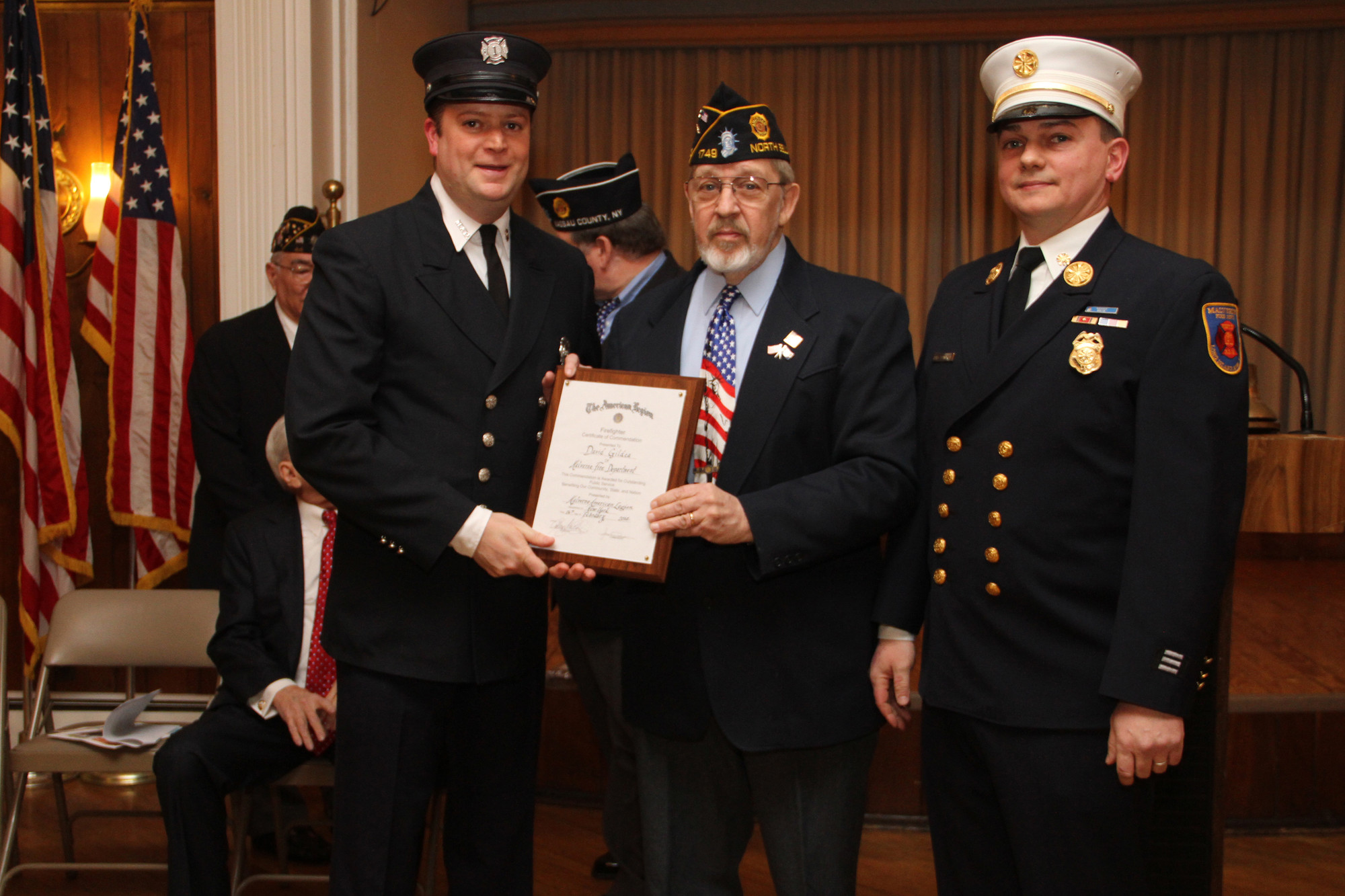 Malverne Fire Chief Scott Edwards and Ron Sabo honored Fireman David Gildea, left, with the Malverne Fire Department award.
