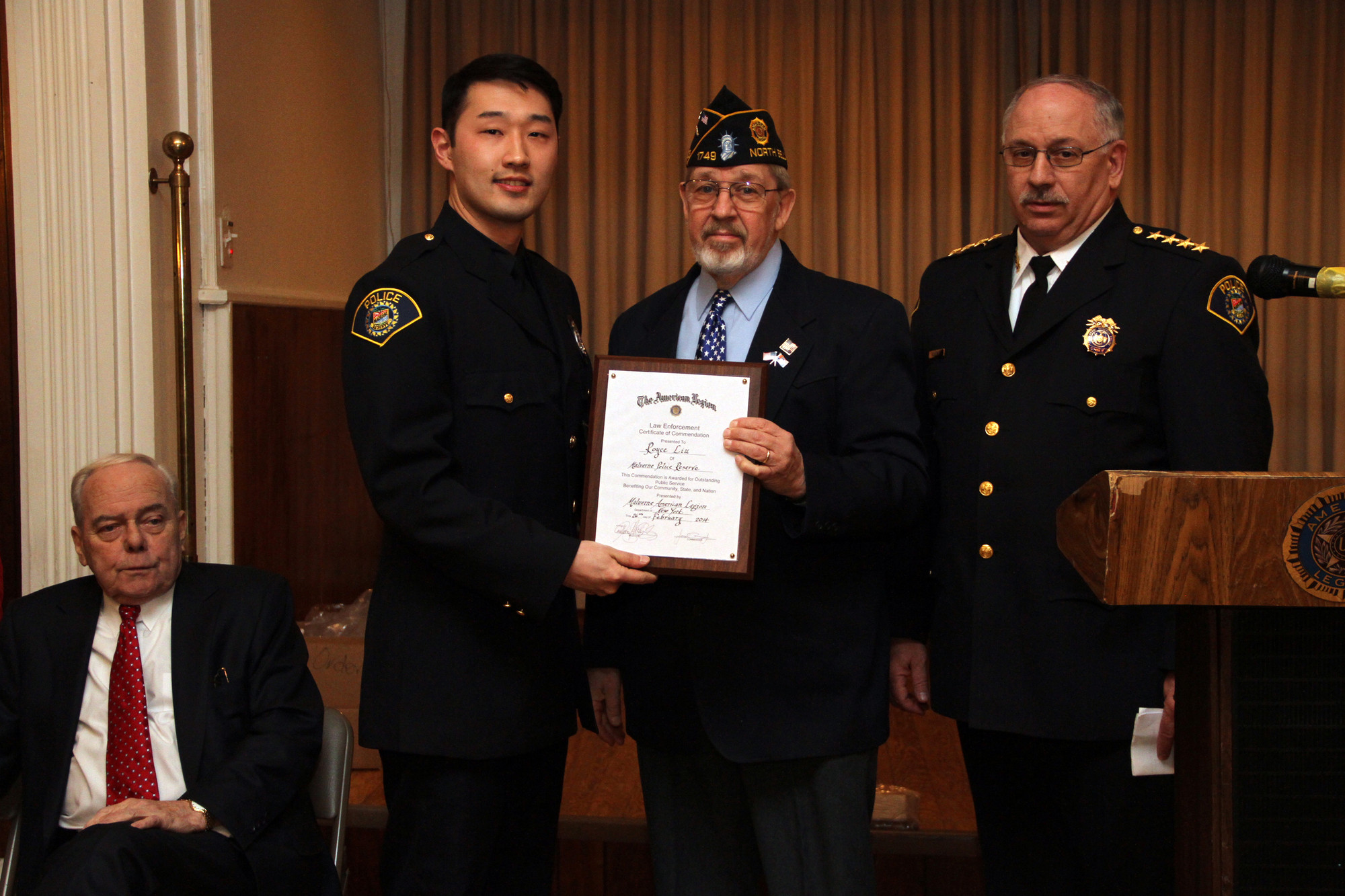 Malverne Police Reserves award recipient R.O. Royce Liu, left, with Ron Sabo and Police Reserves Chief Charles Kaufman.