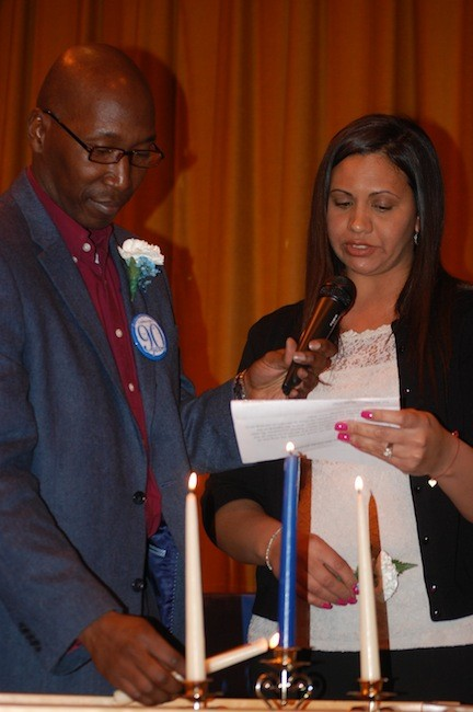 Forest Road PTA leaders Kenroy Woodley and Natalie Cange lit candles in the Founder's Day ceremony.