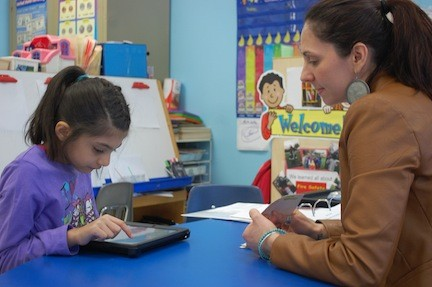 Ansa, with teacher Jamie Lowry, uses the iPad to overcome her limited communication skills.