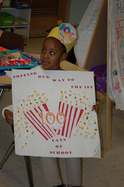 James A. Dever School first-grader Celine Buly showed her classmates the poster she made using 100 kernels of popcorn.