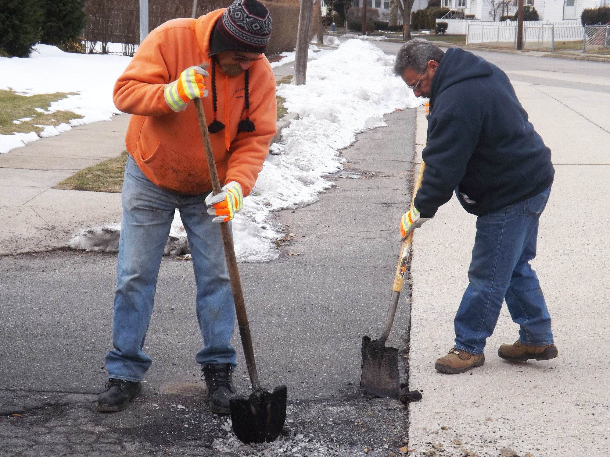 Filling in potholes is currently the No. 1 task for the Valley Stream Highway Department, according to its supervisor Tim Leahy. John Gabrielson, left, and Frank Lopez filled in potholes near the Gibson Long Island Rail Road station last week.