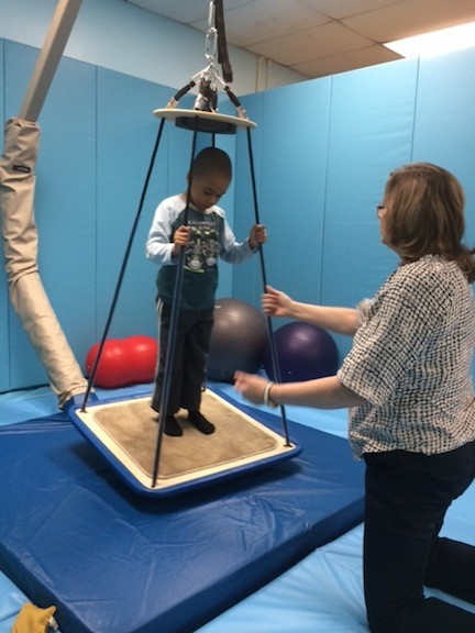 Occupational therapist Patricia Butt works with Michael on the new swing in the sensory gym at Forest Road School.
