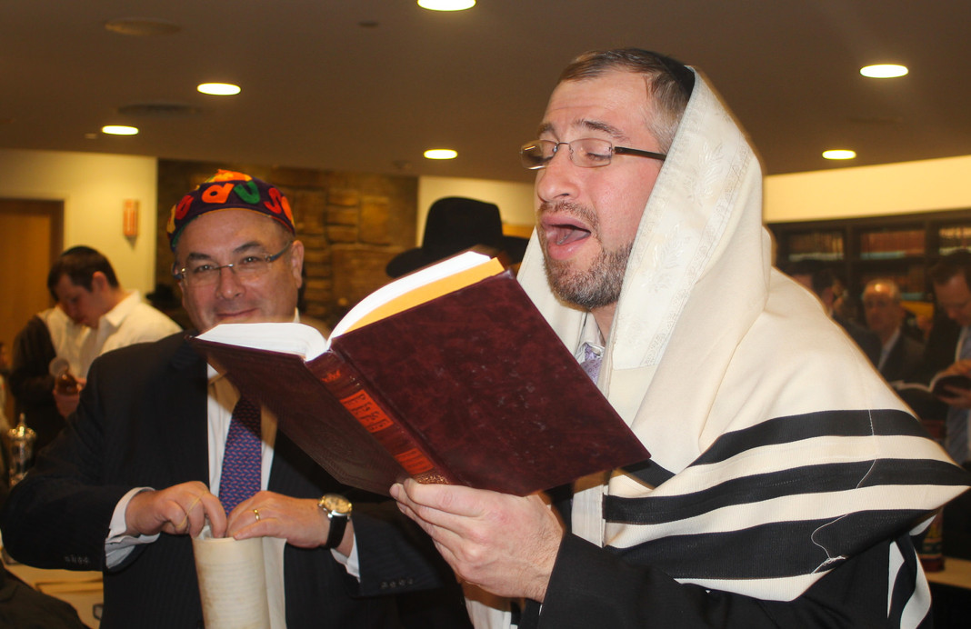 Before reading the Megillah, which chronicles the Purim story, Rabbi Yisroel Kaminetsky read the blessings, at left Heshy Schertz.