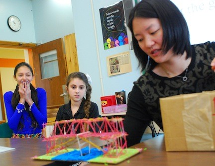 APEX students Samantha Loew, left, and Kendall Satcowitz, both sixth-graders at Levy-Lakeside Elementary School, watched and waited nervously as APEX teacher Sherry Ma added weights to their bridge in APEX's annual Strongest Bridge competition.