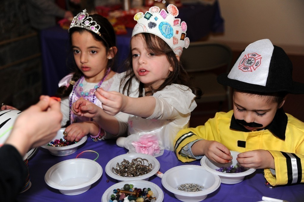 Samantha Scoma, Mirel Kramer and Benyamin Lippman made jewelry at Chabad's recent Purim celebration.