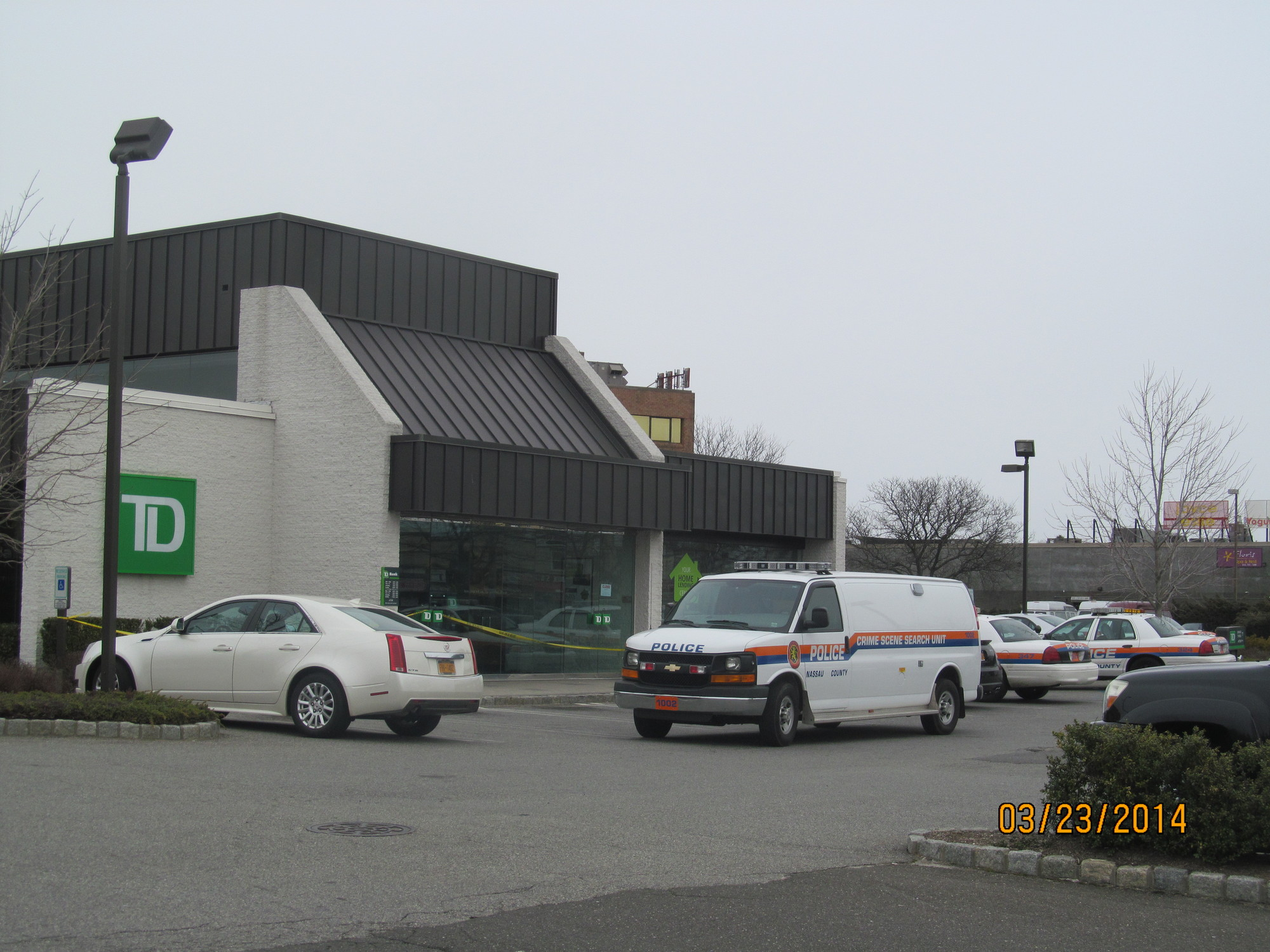 "After robbing TD Bank Sunday, police say a woman fled in a ""dark colored"" car."