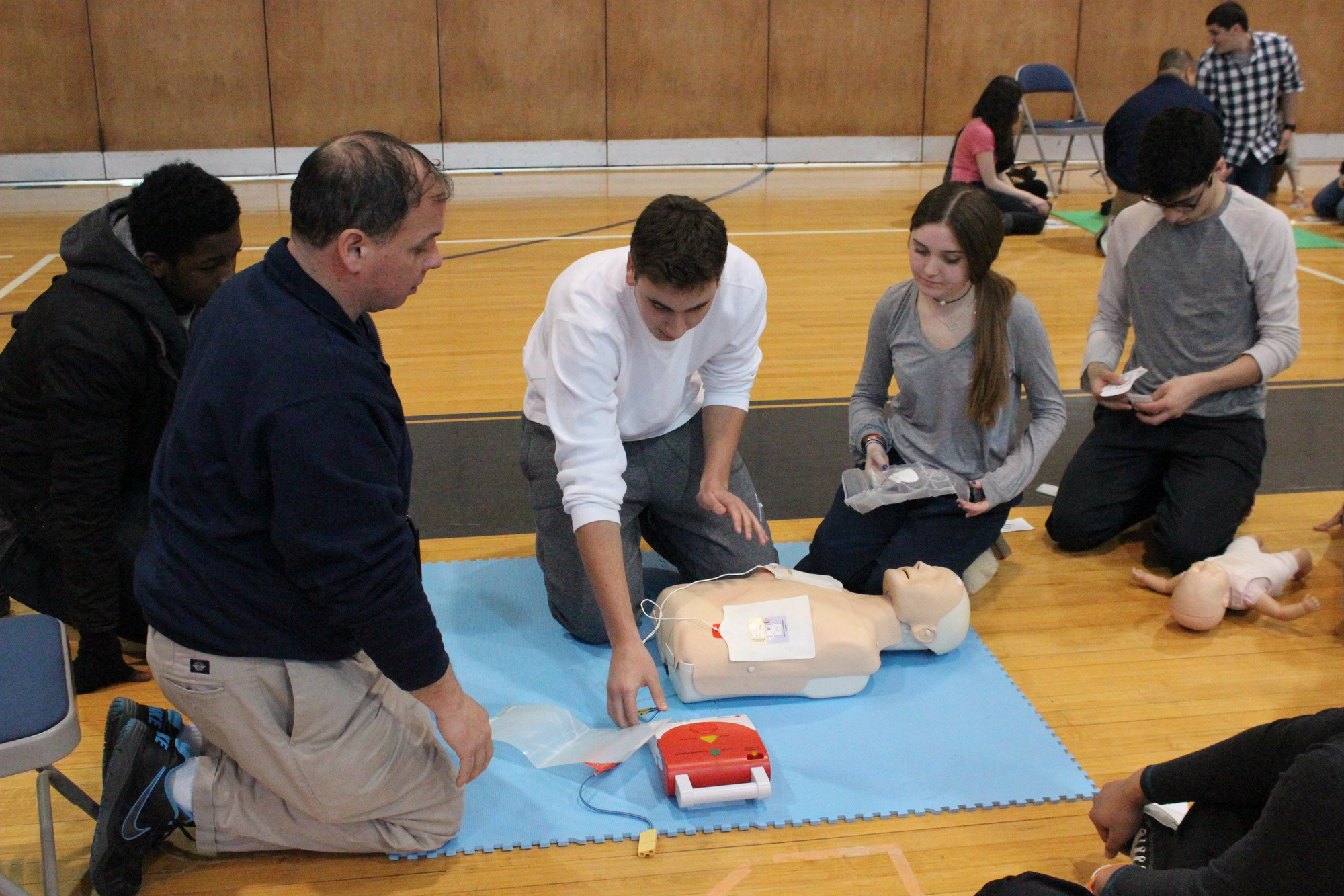 Hewlett High School senior Cory Golden, center, worked with a Safe Health Education instructor and classmates to perform CPR and practiced using an automated external defibrillator device.