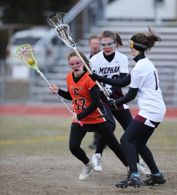 Carey's Tina Yirka, left, looked to avoid a pair of Mepham players during a Conference IV game.