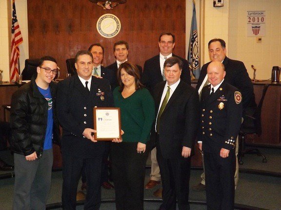 Lynbrook firefighter Michael Kenny saved the life of a 2-year-old aboard a flight to El Salvador in January. He was recognized by the Village of Lynbrook last month for his actions. He was accompanied by his son, Tyler, and his wife, Lisa. He was joined by Lynbrook Mayor William Hendrick, FD Chief Ed Hynes, front row; back from from left Trustee HIlary Becker, Dep. Mayor Alan Beach, and Trustees Tom Aktinson and Mike Hawxhurst.