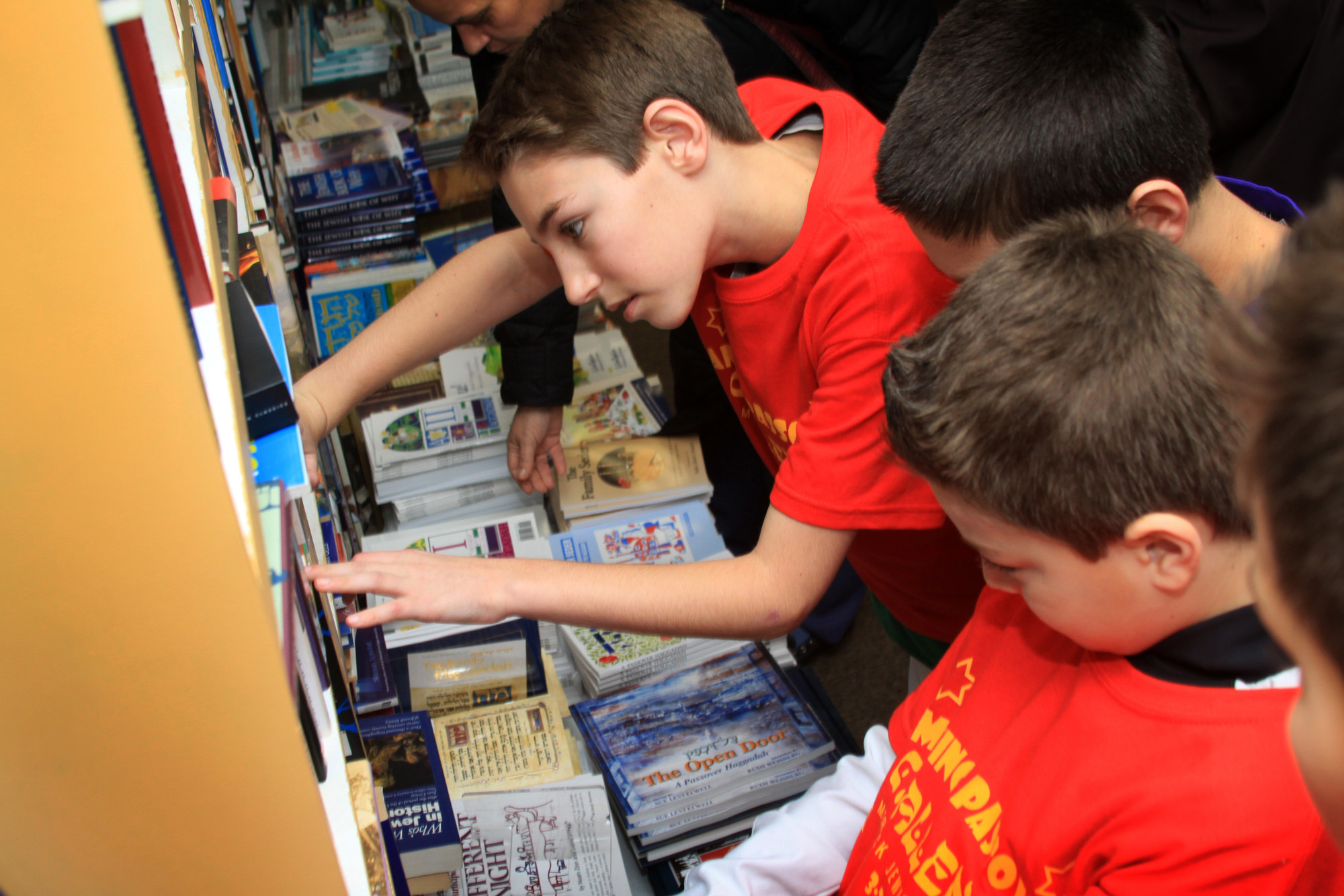 Josh Rosenberg, 12, searched bookshelves at Yussel's Place in Merrick for a copy of MJC Rabbi Charles Klein's book.