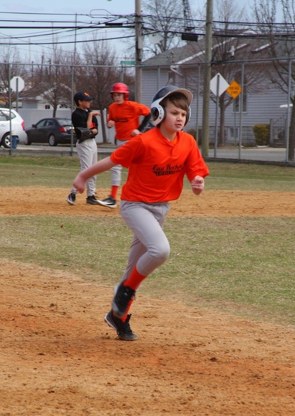 East Rockaway's Orange baseball team No. 24 is Timmy Neckles, making his way to third base.