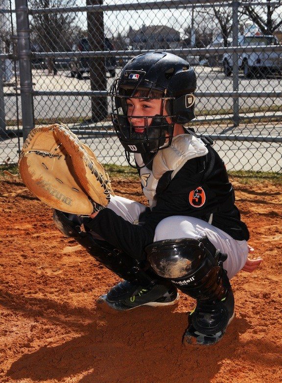 12 year old Richie Madden plays catcher for the black team.