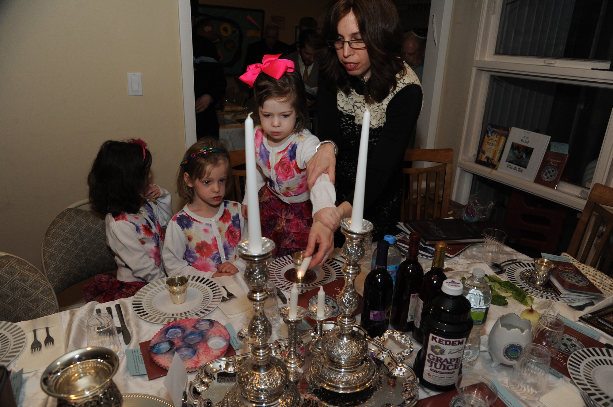 Chanie Kramer, right, lit candles with Mirel, Sarah and Leah before the Seder.