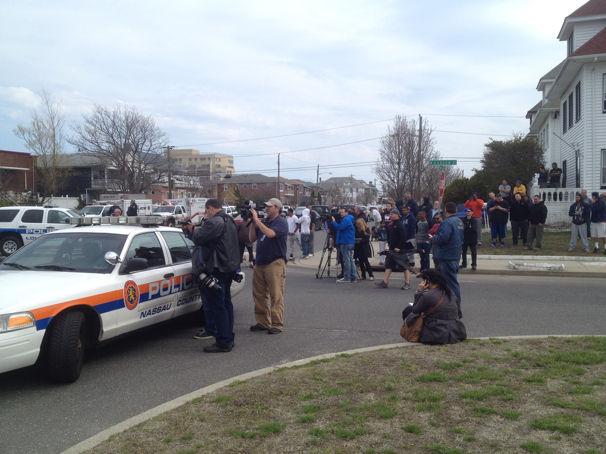 Laurelton Boulevard was teeming with news media on Tuesday, as residents and bystanders milled about near the scene.