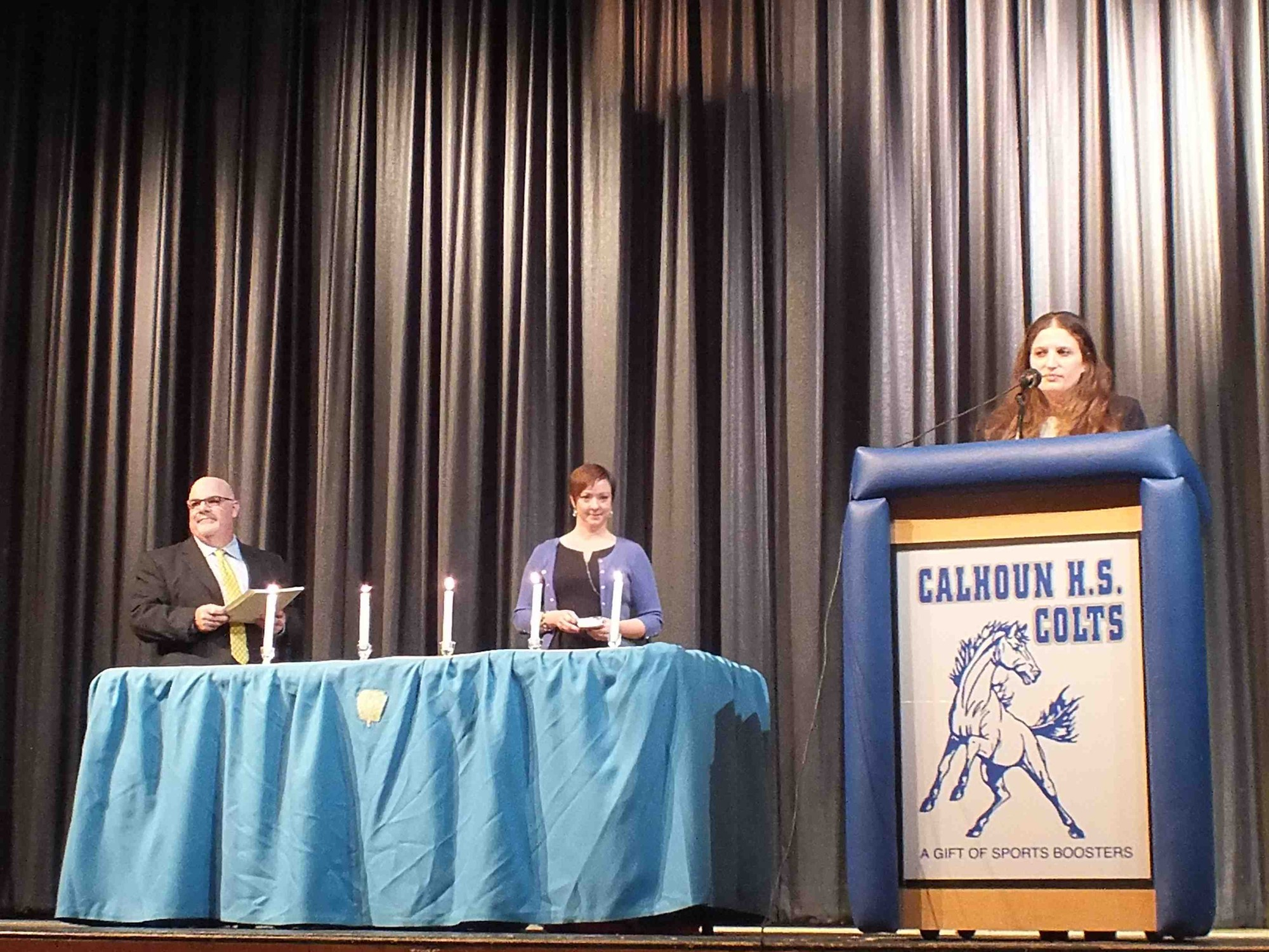 Julie Rosslee, at lectern, the Calhoun National Honor Society chapter adviser, spoke at the ceremony, with Principal David Seinfeld and Assistant Principal Nicole Hollings at back.