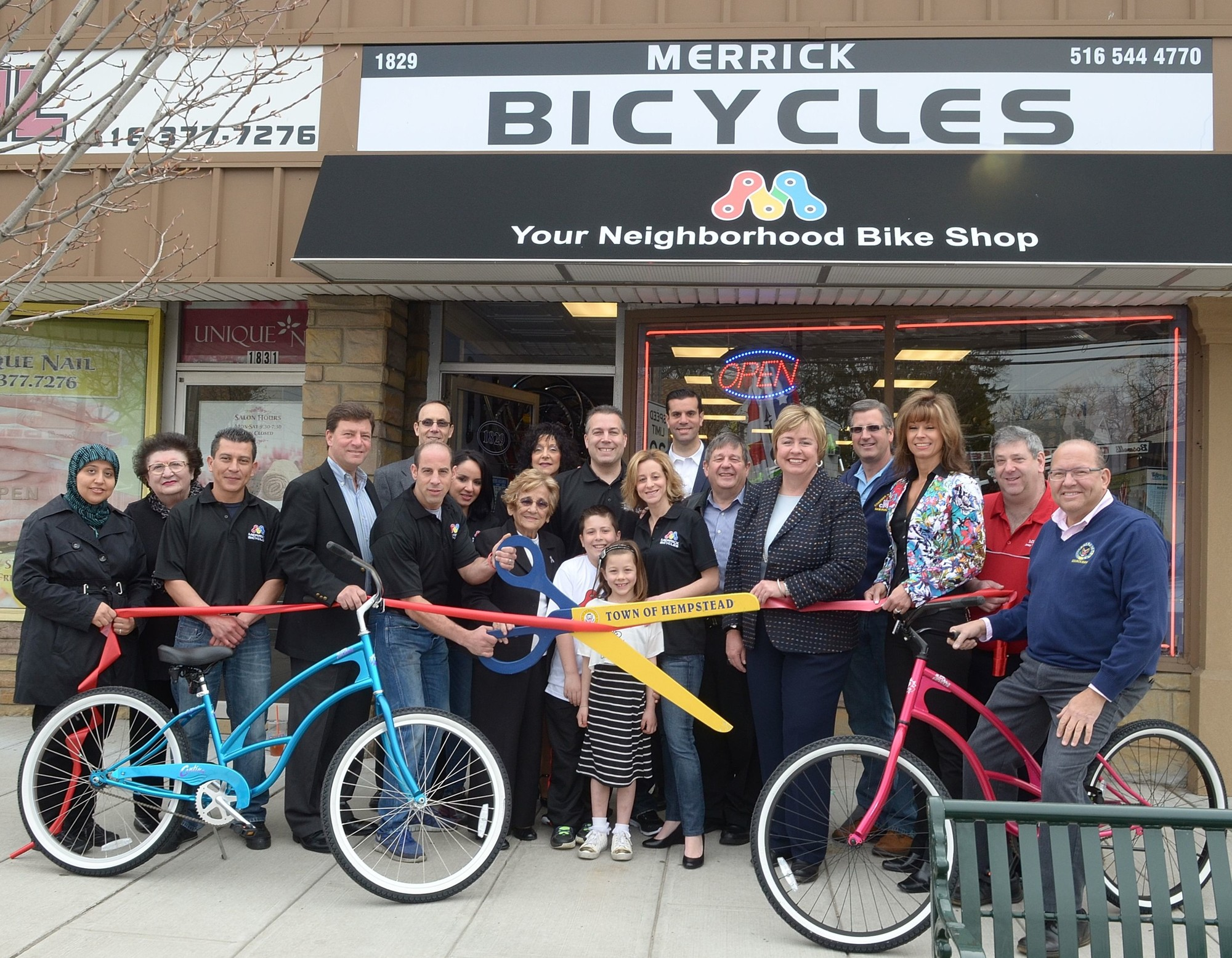 Town of Hempstead Supervisor Kate Murray, fifth from right, joined  Merrick Bicycles owners Mike Hammer, fifth from left, front, and Dan Yuricic, center, their families, other elected leaders and Chamber of Commerce officers in officially opening the business.