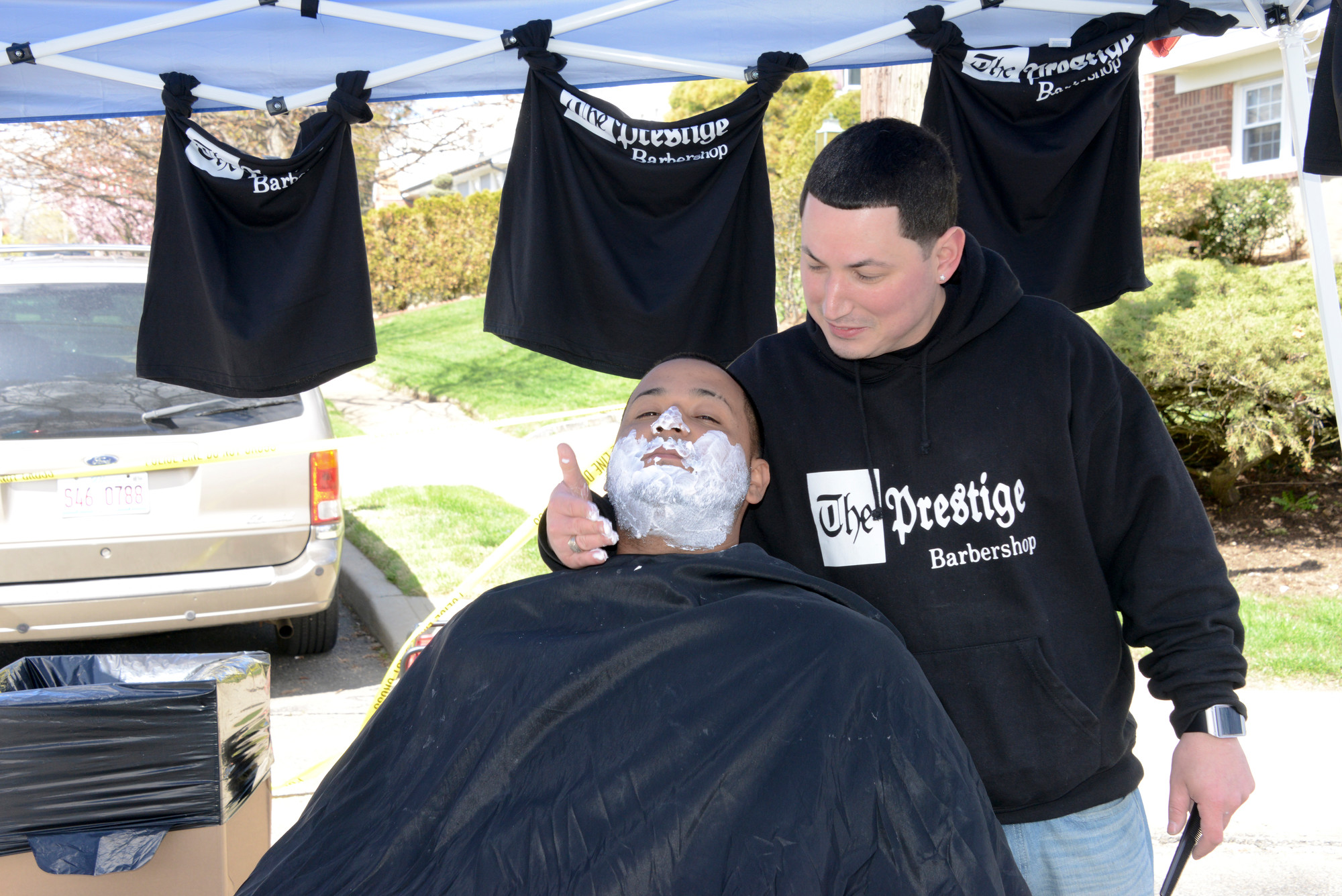 Prestige Barbershop Owner Alex Alvarado gave Jordan Alzate a free shave and haircut at the West Hempstead Lions Club Street Fair last Sunday.