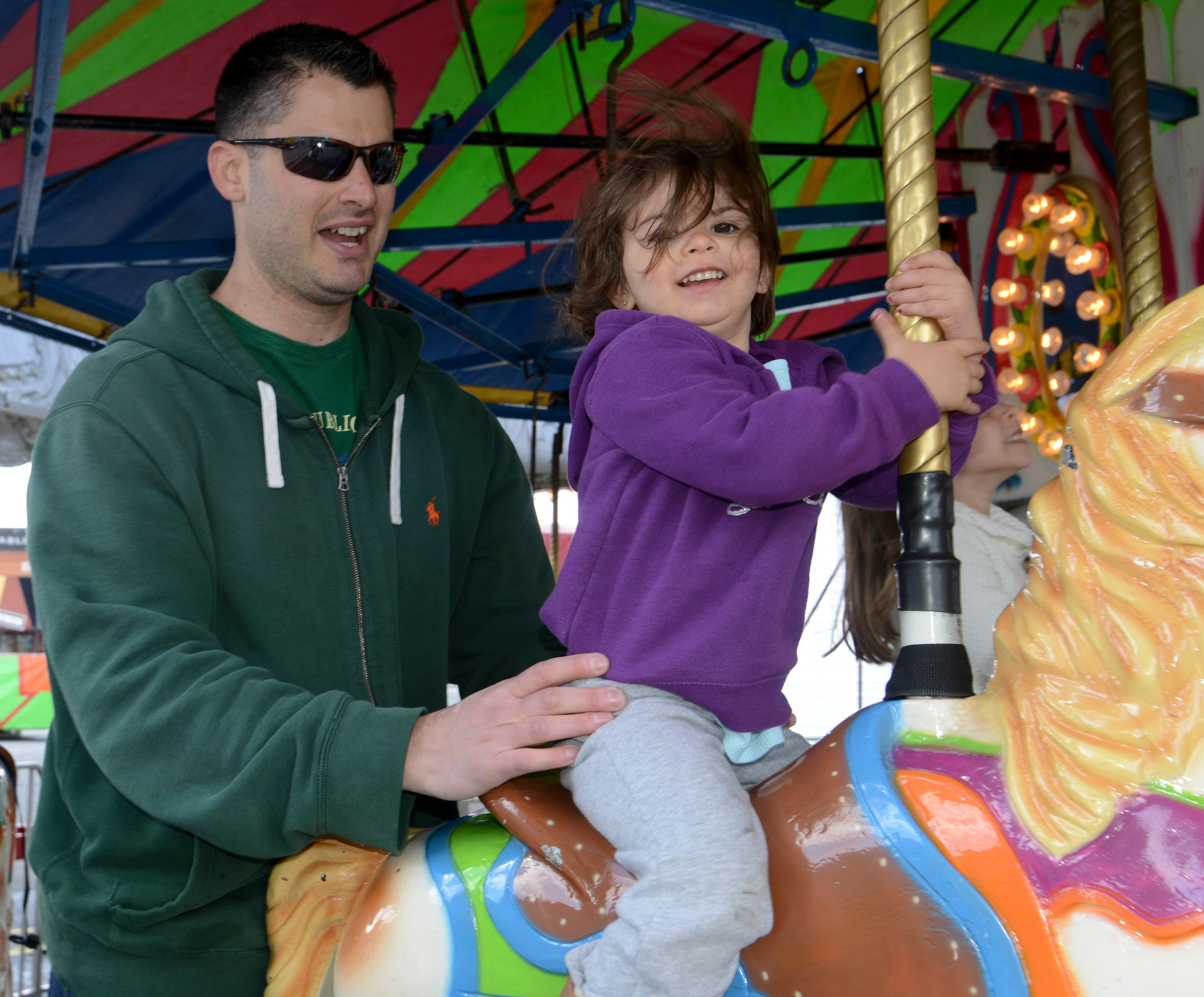 Nick Pecoraro gave his 2-year-old daughter, Grace, a hand on the merry-go-round at Kids Festival. The event serves as a scholarship fundraiser.