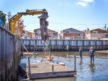 A group of volunteers removed a decrepit dock, above, and other debris from the Heron Street canal last Saturday, part of the Surfrider Foundation's annual Earth Day cleanup.
