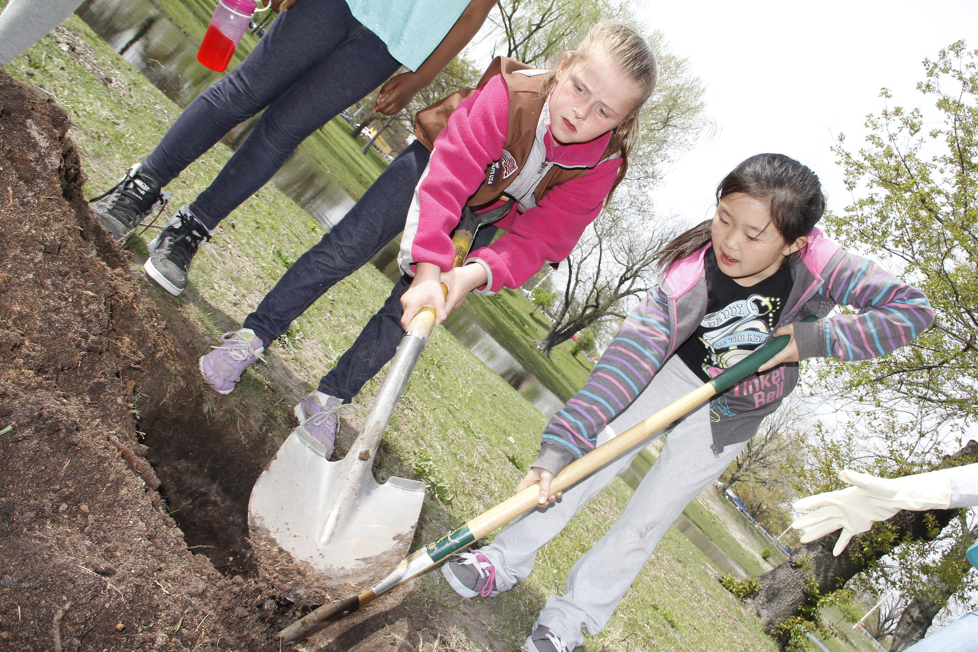 Fiona Casucci and Madeline Yeh from Brownie Troop 2073 helped dig the hole where a new tree will be planted.