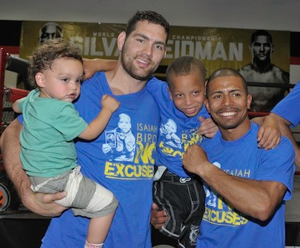 Weidman, left, holding his son C.J., with Bird and Long Beach Gladiators coach Miguel Rodriguez at the fundraiser.