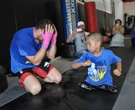 UFC Champion, left, sparred with 6-year-old Isaiah Bird, a member of the Long Beach Gladiators wrestling team, who was born with a defect that left him without legs. Weidman held a fundraiser last Sunday for Bird and his family, who are currently living in a Freeport shelter.