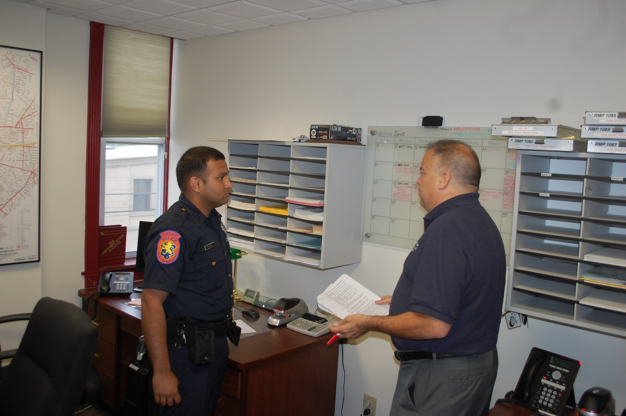 Auxiliary Police Officer Mohammed Shaikh, left, and Commander Richard Vela look over the schedule in their top floor office.