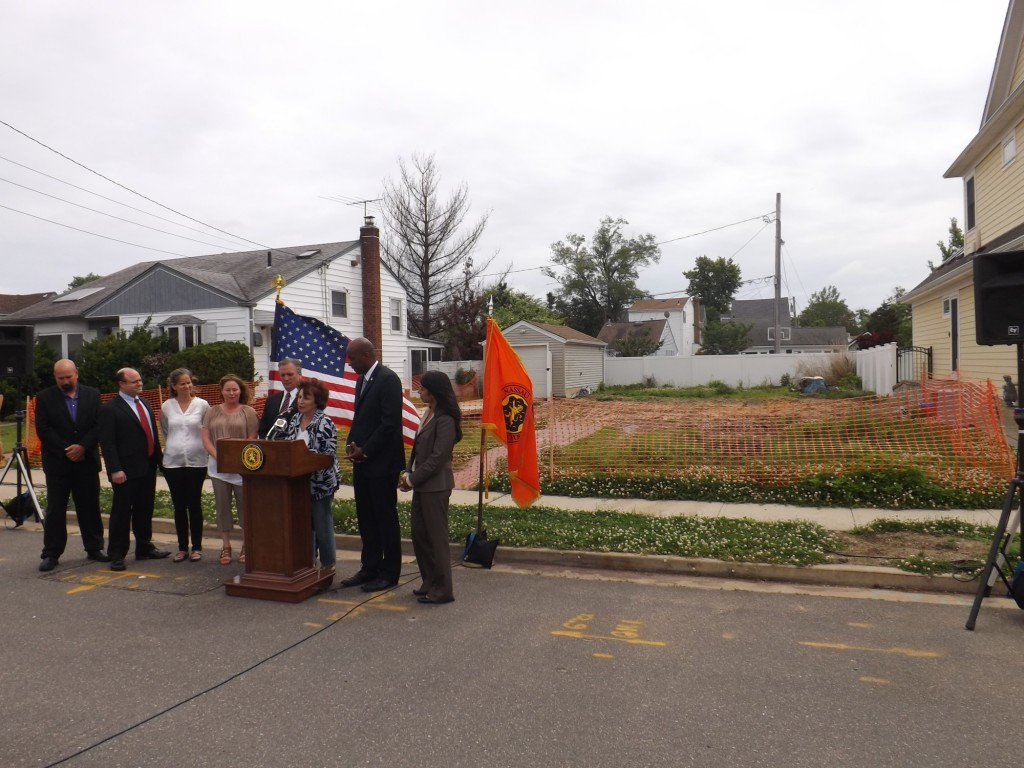 County officials announced a bipartisan deal to re-establish the Clean and Seed program in front of an East Rockaway property, at right, that is vacant as a result of Superstorm Sandy.