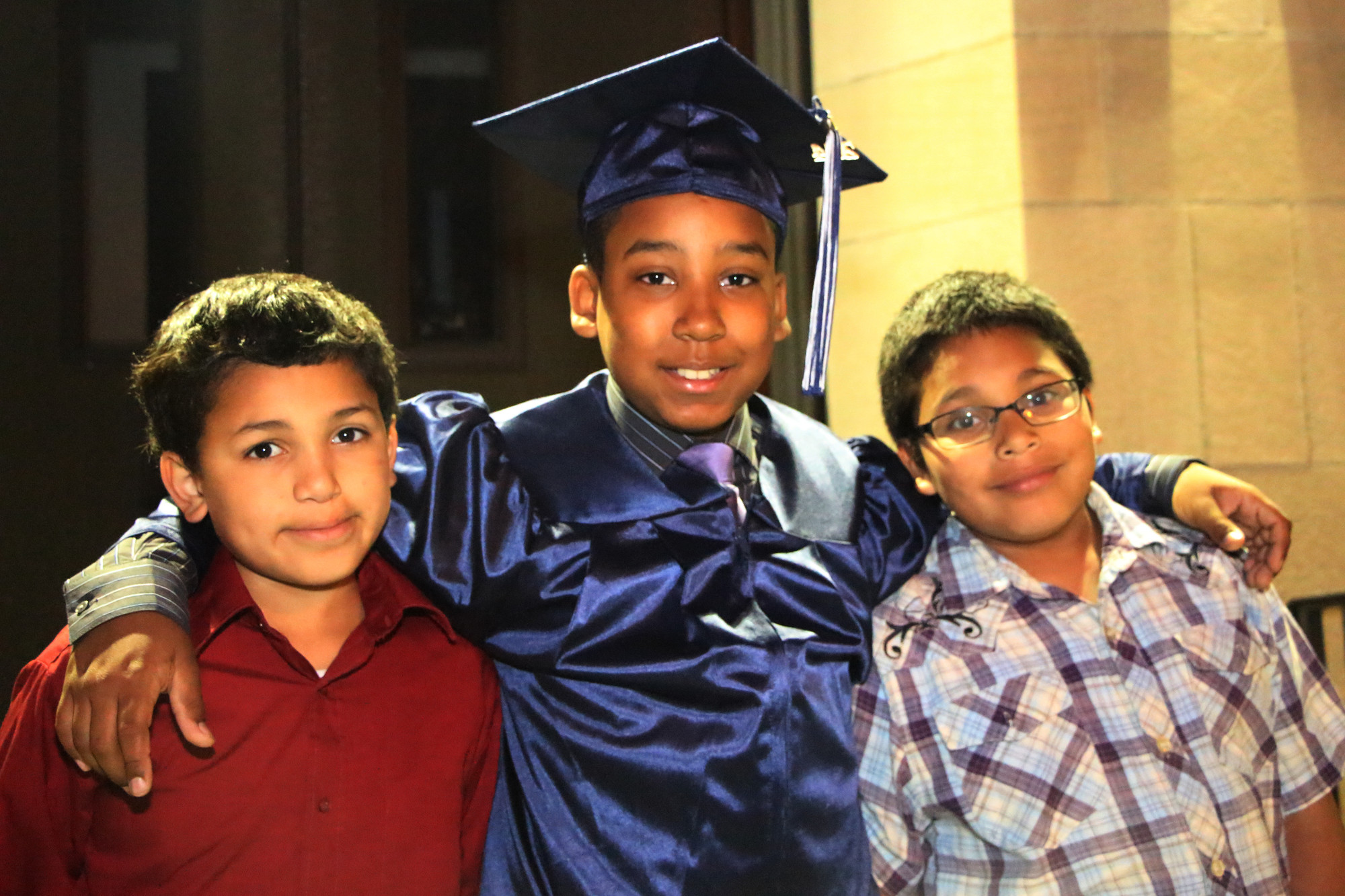 Graduate Michael Valenzuela  ,13, with his cousins, Adrian Rivera,10, and Jonathan Rivera, 9yrs, following the ceremony on June 12.