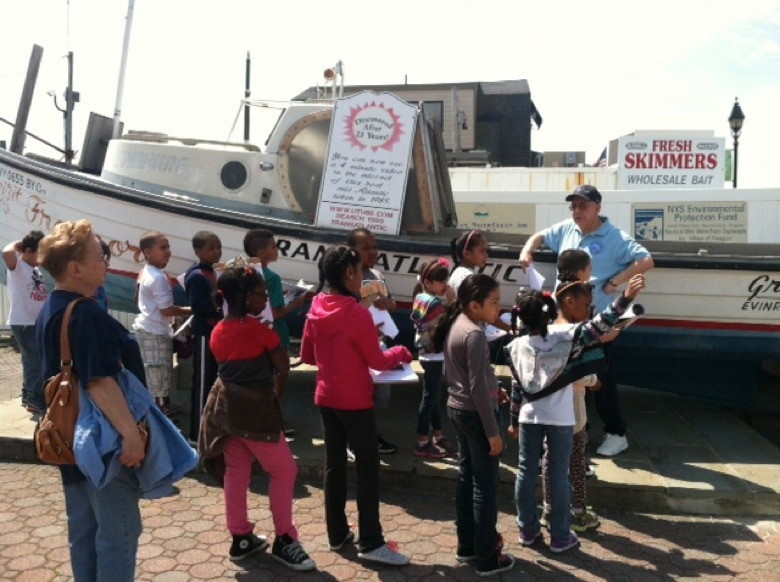 Student scientists take a walk along the Nautical Mile with Captain Block.