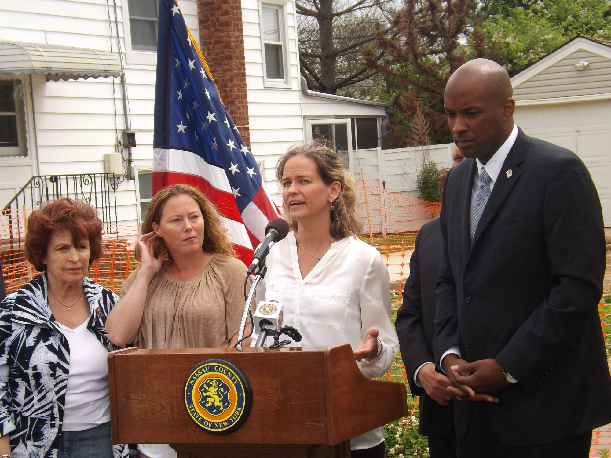 Legislator Laura Curran, second from right, and her colleagues in the County Legislature, including Norma Gonsalves, far left, and Kevan Abrahams, at a press conference in front of the property of East Rockaway resident Theresa Gaffney.