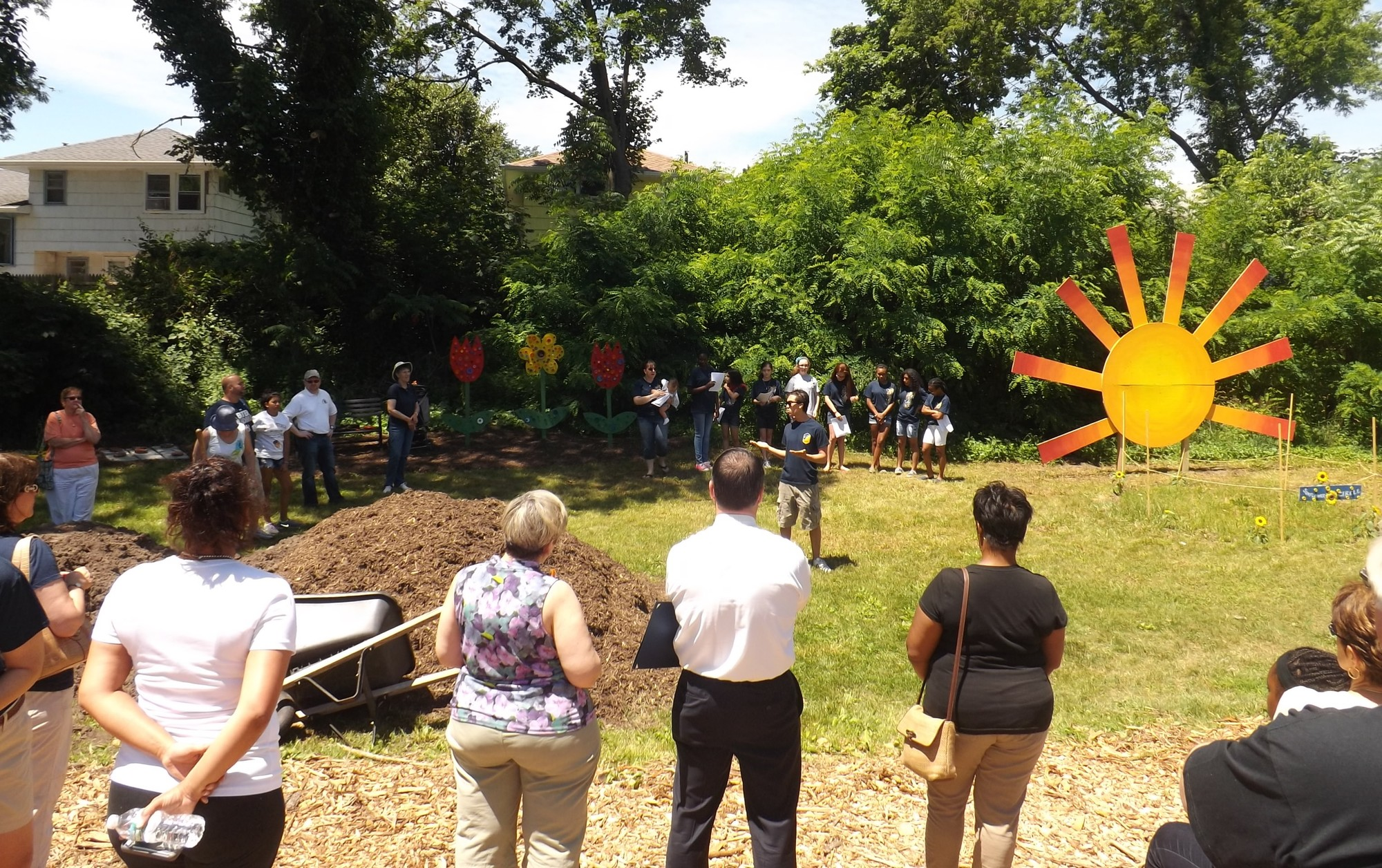 The Baldwin Civic Association hosted a ceremony on June 21 to open its new community garden behind the Baldwin Historical Society Museum, off Grand Ave. BCA President David Viana, center, welcomed residents and thanked those who helped create the garden.