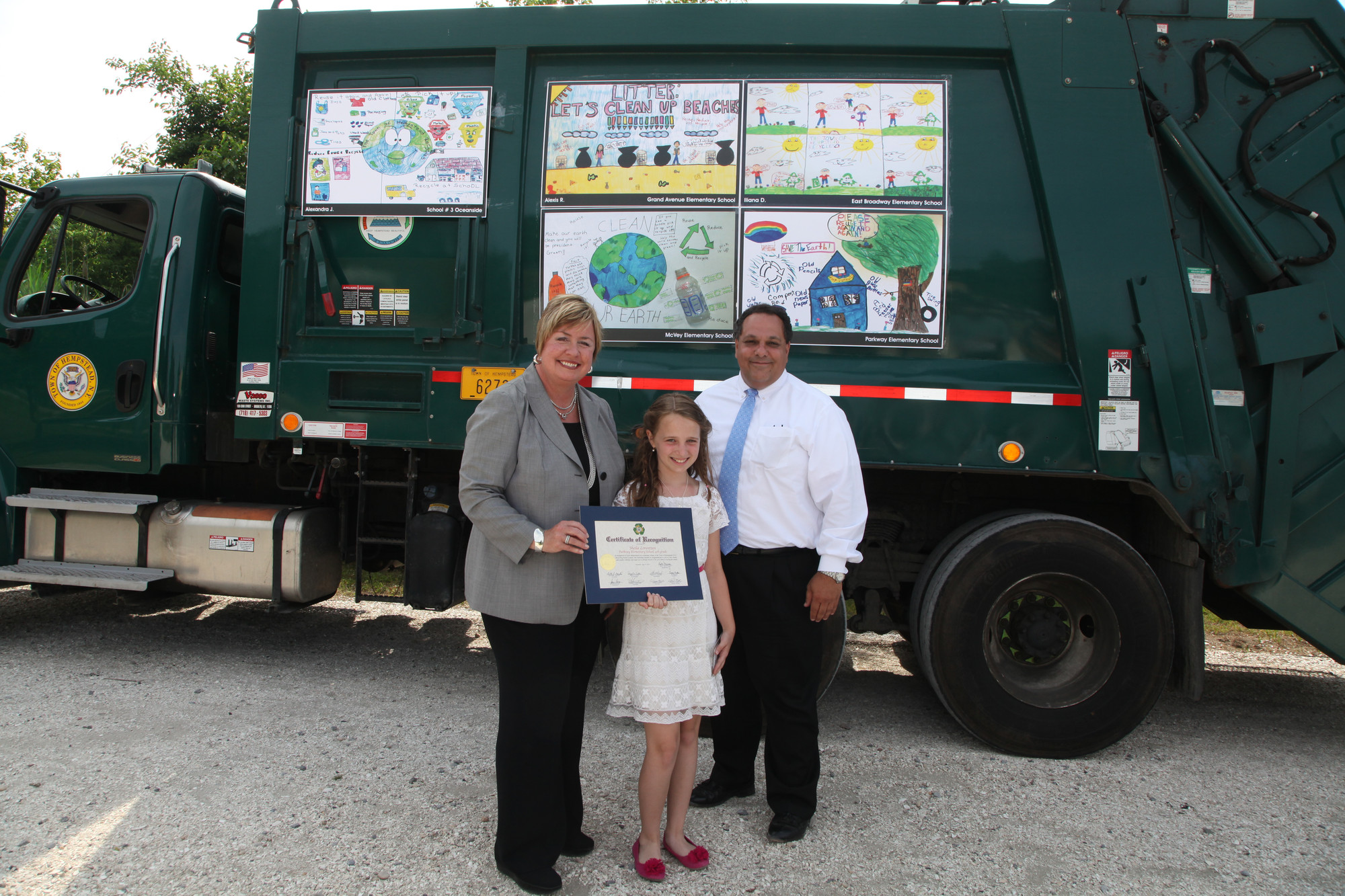Sheila Lorentzen, of Parkway Elementary School, with Supervisor Murray and Anthony Core of Westbury Paper Stock.