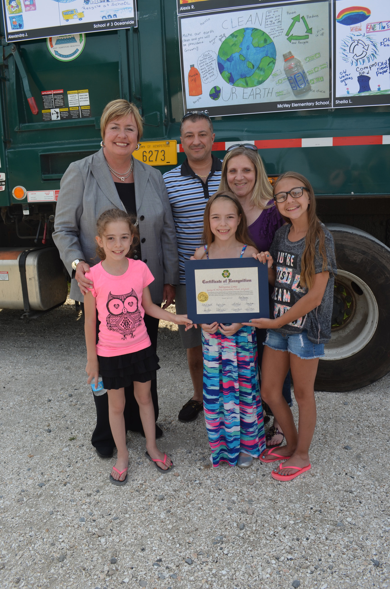 Adrianna Como, a third-grade student at McVey Elementary School, holds her award while surrounded by her family and Town of Hempstead Supervisor Kate Murray.