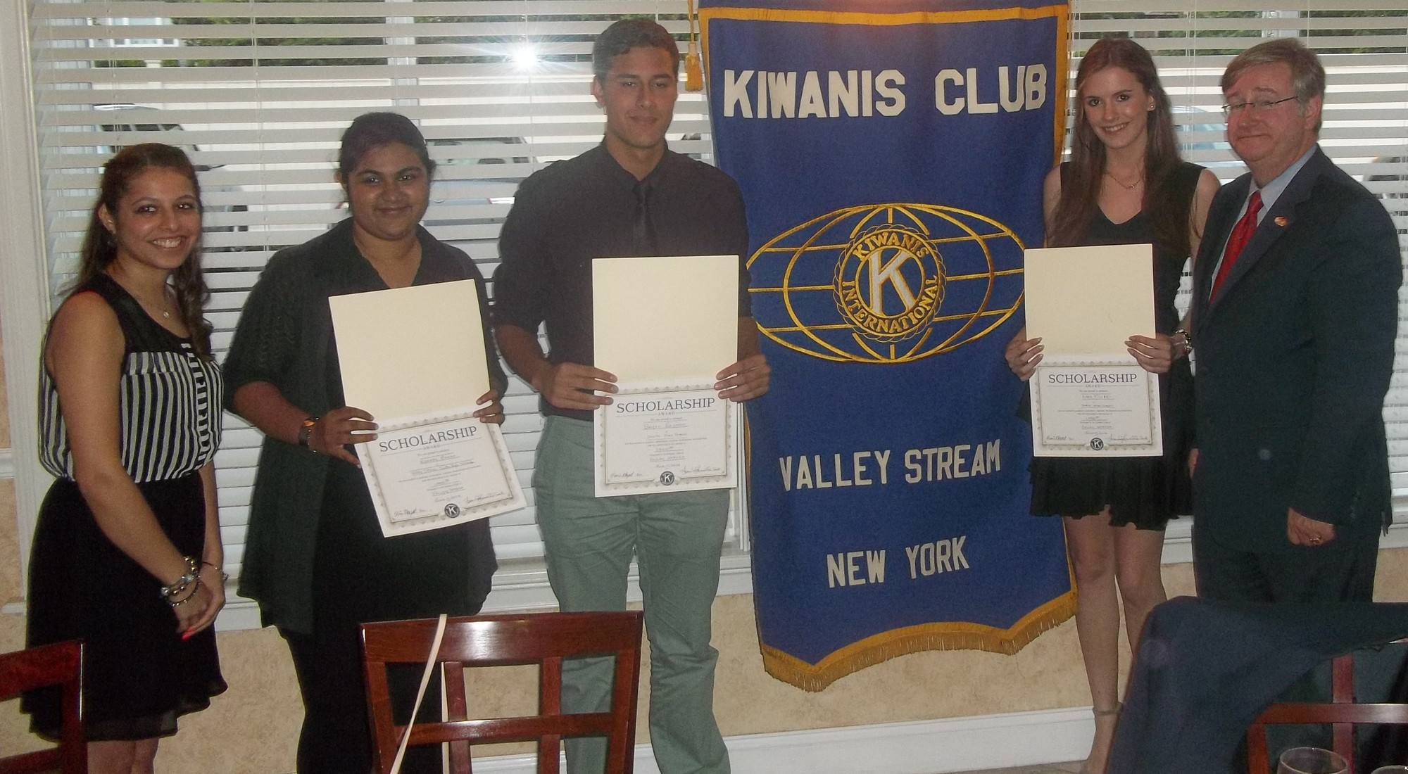 Kiwanis Club President Karin Hayat, left, presented South High School seniors Moneba Zaman and Bryan Rosado and North senior Kara Filippi with college scholarships. Village Justice Robert Bogle, right, said a prayer before dinner.