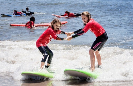 Isabella Gillam, left, and Lizzie Schmidt, both 11, rode a wave together at Long Beach Boulevard beach during International Surfing Day on June 20.