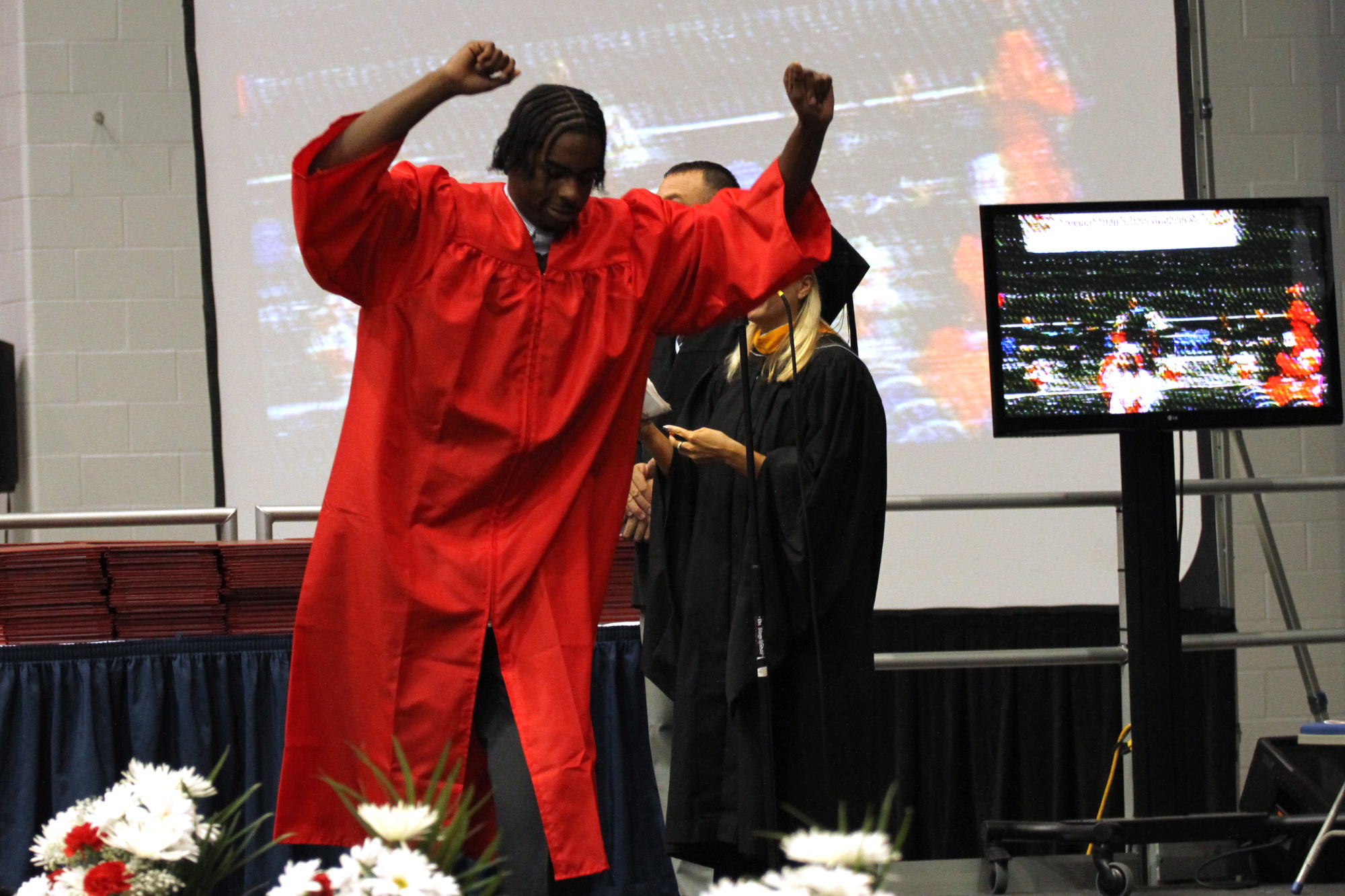 Nicholas Harrison throws his hands up in celebration as he graduates