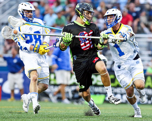 The Lizards' Kyle Hartzell, center, sliced through Florida's Peter Ricci, right, and Stephen Keogh, during the team's 20-11 victory on July 3.