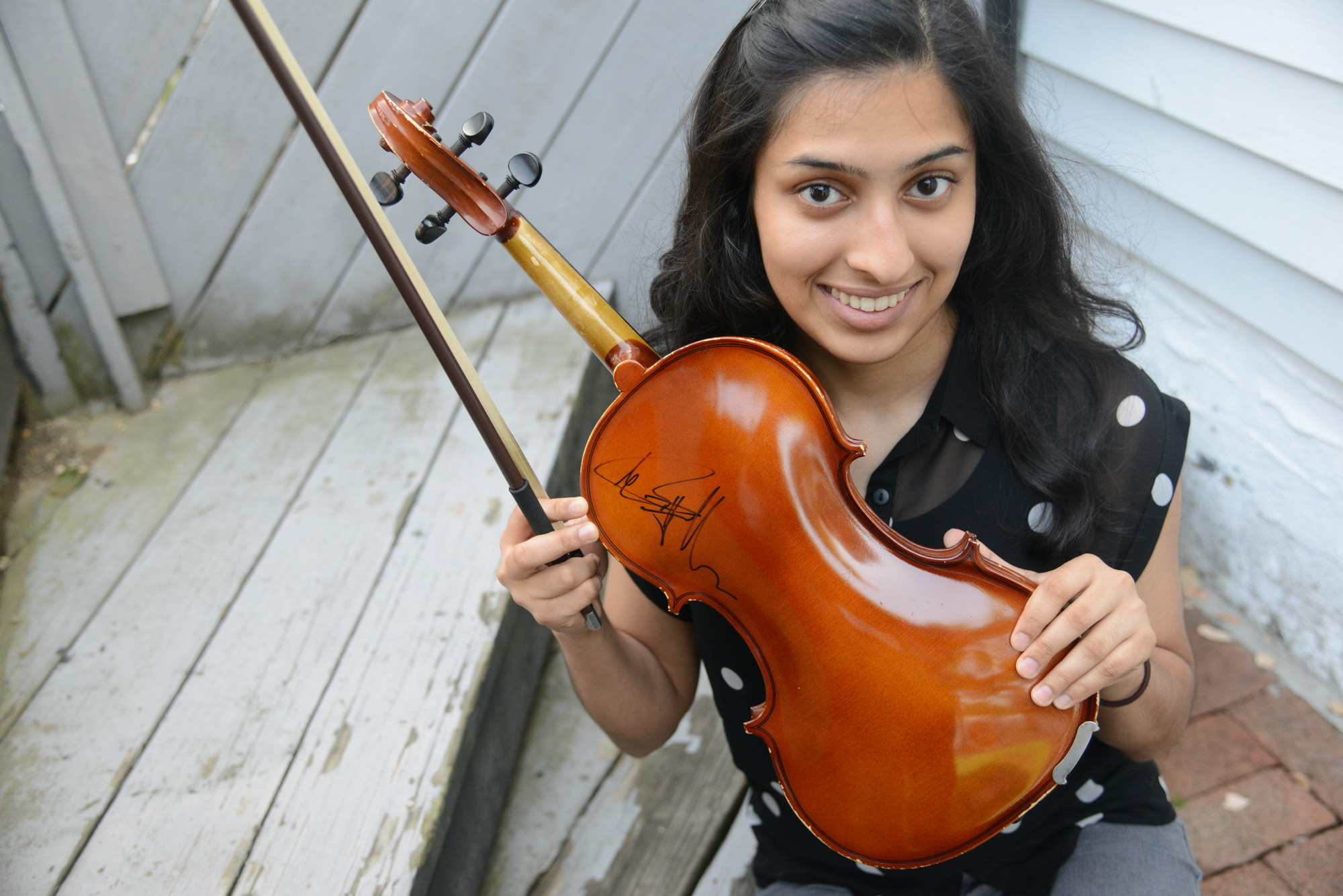 The sisters played at the NYCB Theatre in Westbury last December with the Piano Guys, a musical duo that combines classical and pop music. The group autographed Binita's violin.
