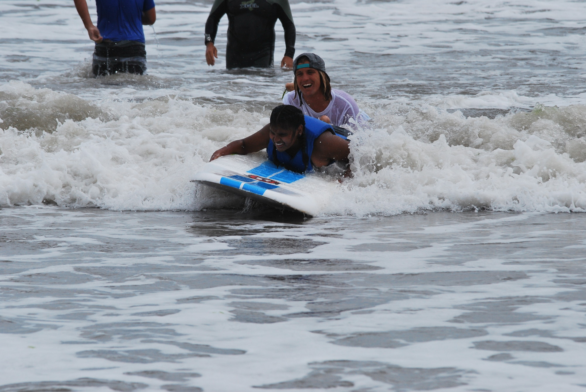 Jessica Karim rides in with professional surfer and Surf for All volunteer TJ Gumiela.