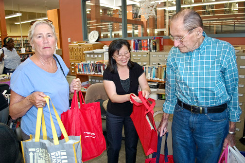 Librarian Lena Sau, center, handed bags of books to volunteers Jean Rechner and George Ellard to be delivered to homebound residents of Valley Stream.